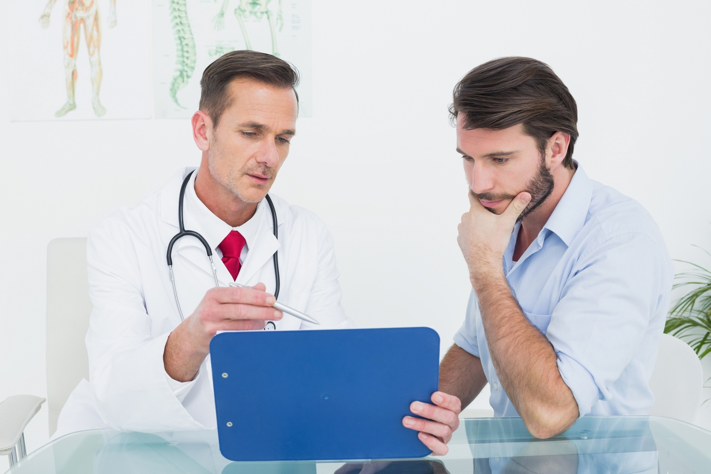 Male doctor discussing reports with patient at desk in medical office
